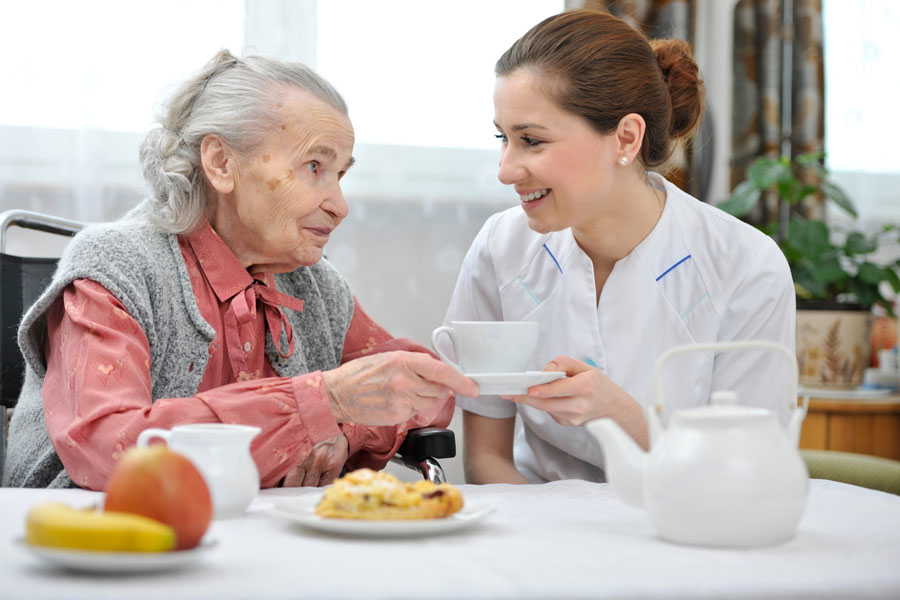 Berufliche Pflegesituation: Pfegerin und alte Frau