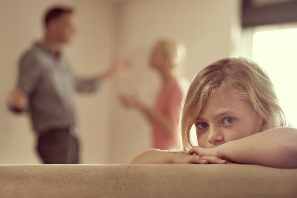 Kind und streitendes Elternpaar im Hintergrund