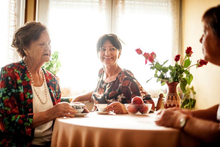 Seniorin, Tochter und Pflegerin beim Kaffeeplausch