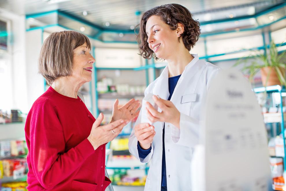 Apothekerin berät und vermittelt ältere Frau an Seniorenzentrum