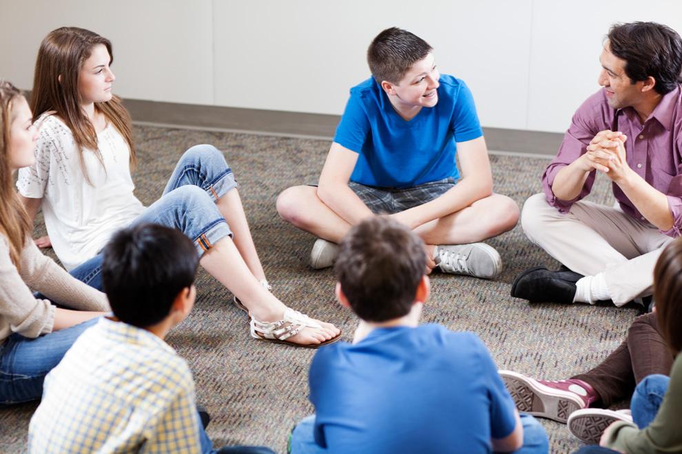 Schüler_innen und Lehrer sitzen im Kreis