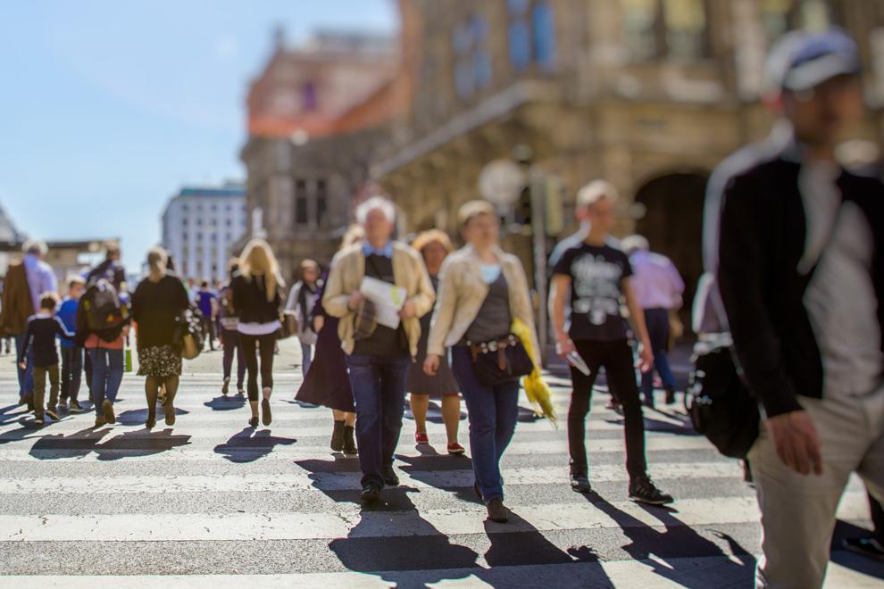 Personen überqueren in Gruppen einen Fussgängerstreifen
