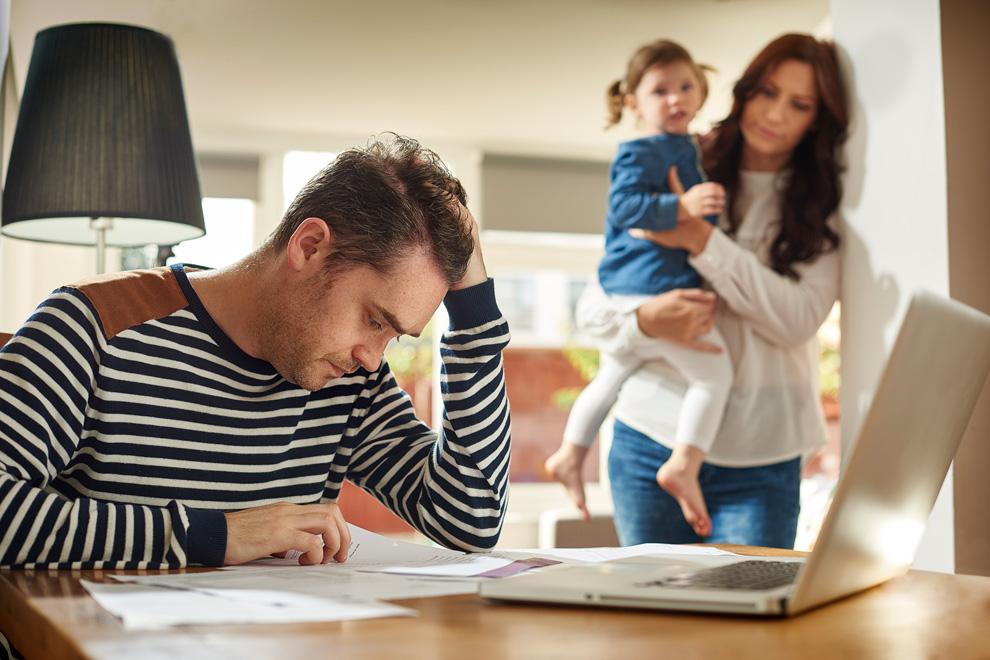 Gatte studiert Steuererklärung, beobachtet von Frau und Kind