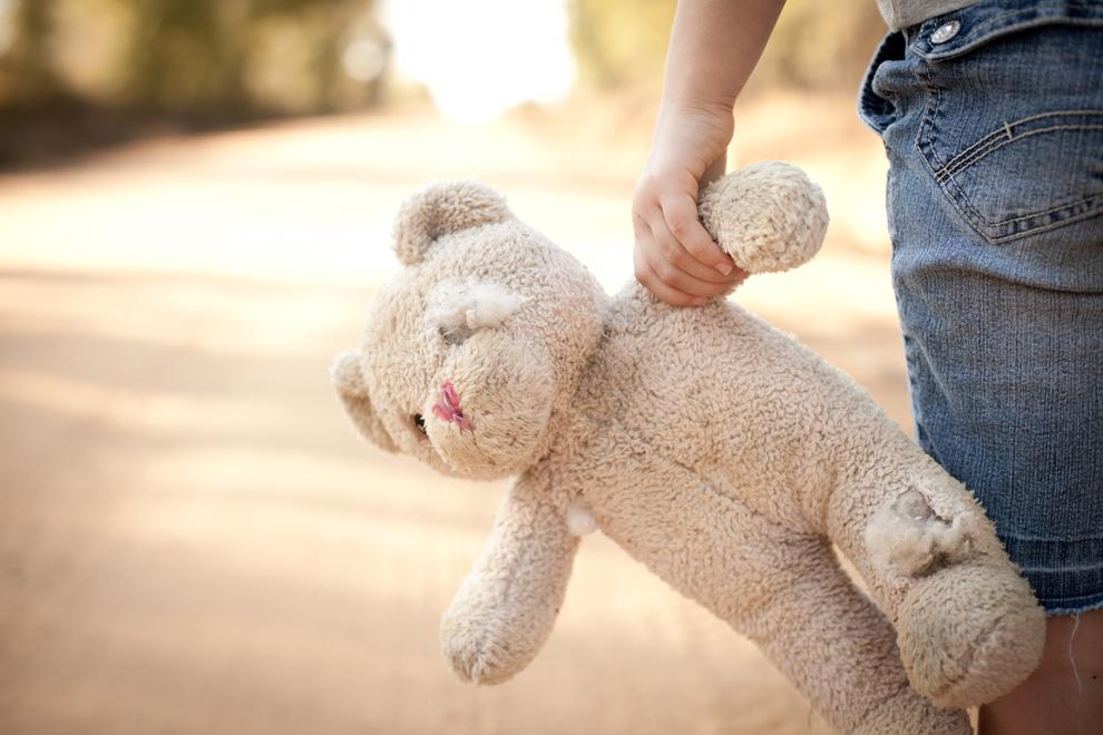 Kind mit lädiertem Teddy auf der Landstrasse