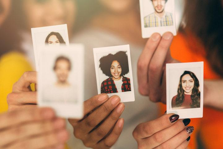 Jugendliche halten Fotos von sich in die Kamera